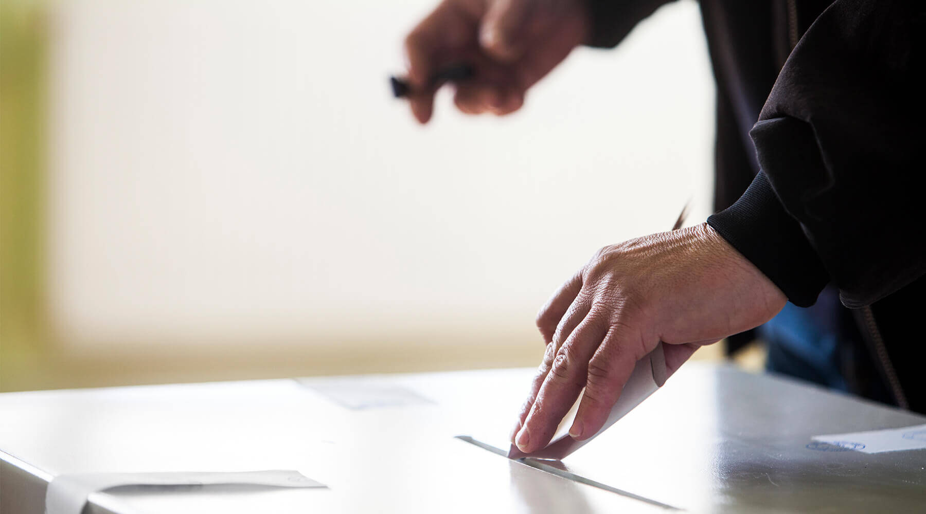 Person putting their vote for mayor in the ballot box